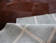Rectangular patchwork cowhide rug with square shape inside in reddish brown tones for a more intimate room look.
