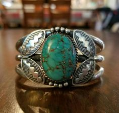 Native American Carico Lake Turquoise and Silver Cuff Bracelet. Navajo handmade from sterling silver and natural Carico Lake turquoise. Measurements are approximately 1 7/8 inches wide across face >1 3/4 inches tall 2 3/8 inches length >5 5/8 inches inner circumference 1 1/8 inches gap. Total circumference is inner plus gap. Bracelet can be minimally adjusted to fit. Signed R J