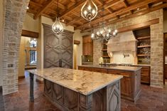 Old world italy inspired kitchen with wood beams, cotto tiles, stone and featured lighting. Austin TX. #VanguardstudioInc