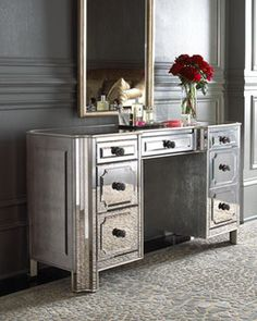 Antique mirrors add sparkle to a piece that works easily as a vanity or a desk. Made of select hardwoods with silver-leaf trim and antiqued silver hardware.
