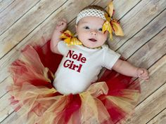Florida State University Garnet and Gold Nole baby girl outfit. The white bodysuit can be long sleeve or short sleeve and can be personalized with your little ones name. The tutu can be made with a solid gold ribbon instead of the ribbon with arrows. The tutu is garnet and gold tulle and this set has a matching headband out of garnet and gold ribbon with a football in the center of it. If you would like this personalized please put your childs name in the notes on the order exactly the way…