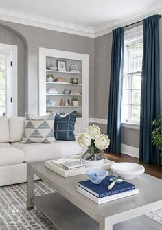 Wonderfully styled living room features a white linen sofa accented with white and blue and placed on a white and gray striped rug facing a gray wooden coffee table. Navy And White Living Room, Grey Walls Living Room, Blue Living Room Decor, Living Room Accents, Living Room Color Schemes, Living Room Grey, Living Room Sofa, Living Room Designs, Curtains Living