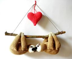 Stuffed sloths couple on a branch with red heart, cute gift crochet sloths