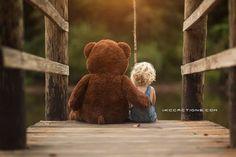 Фото Ребенок с игрушечным мишкой сидят на мостике, фотограф Kevin Cook