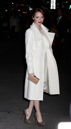 Emma Stone embraces winter white in a double-breasted trench with extra-large lapels.