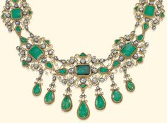 (DETAIL) AN ANTIQUE IBERIAN EMERALD AND DIAMOND NECKLACE Composed of a series of graduated scrolling openwork panels, each set with a foiled rectangular-cut emerald centre, and further fancy-cut emerald and rose-cut diamond accents, suspending a tapering fringe of seven pear-shaped emerald drops, closed set throughout.