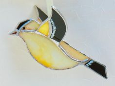 This yellow stained glass 3D goldfinch bird would be the perfect mothers day gift. Create a sunny spot on your porch or in your spring garden. It makes a wonderful gift for the gardener or bird lover.  It is made from a pretty lemon yellow opalescent glass with black glass used for the wings, tail, and head patch. The beak is golden. I painted white feather markings on the wings and tail. It is 5 long and about 3 from wing tip to wing tip. The tiffany method was used in its construction…