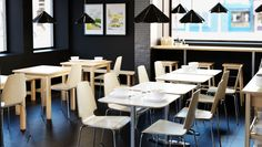 Sushi bar furnished with small tables in white and birch and birch veneer chairs