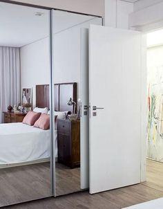 Aqui, o espelho reveste as portas de correr do armário e dá a impressão de duplicar o quarto. Projeto da arquiteta Julliana Camargo