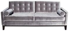 Hollywood-regency-silver with a hint of purple tuffed sofa.  Idea:  In addition to solid cylinder pillows, have a set made in the same fabric as chairs.