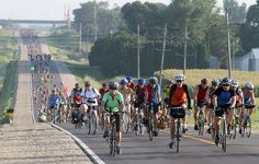 Riders make their way along the RAGBRAI route with helmets on.