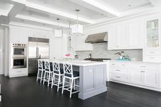 Large white kitchen with a dark walnut stained floor features a gray island topped with a white marble countertop seating four white bamboo counter stools with black seat cushions facing an island sink with an oversize polished nickel gooseneck faucet lit by Caged Medium Lanterns hung from a beadboard ceiling accented with white wood beams.