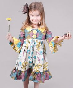 Pretty as a peacock and as bright as a sunflower, this cotton frock is full of color and cheer. Featuring giant front buttons and bell sleeves, it's ever ready for a fun flight of fancy.