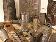 A variety of antique tin graters and nutmeg graters.