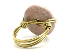 Dive into earthy love with your new chunky Pink Jasper ring. This is natural spotted pink and white stone, polished into a smooth donut and wrapped in gold-plated copper wires. The handmade ring is one-of-kind and sure to make a statement! Jasper is known as a nurturing stone, providing support during times of stress and illness. This one-of-kind ring was handmade in the Satin Crystals studio in California, USA. Ready to gift in a Satin Crystals gift box. Size 8.75 (stone: 1.1 inches). Wire Jewelry Rings, Copper Wire Jewelry, Handmade Wire Jewelry, Rock Jewelry, Gold Wire, Sea Glass Jewelry, Wire Wrapped Jewelry, Diy Jewelry, Homemade Jewellery