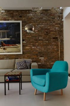 The blue Jonah Armchair sits perfectly in Chloe's neutral living space with an exposed brick wall | made.com/unboxed