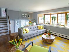 As seen on HGTV's Kitchen Cousins, this renovated living room is filled with color and life. A contemporary gray couch and a cheery chevron carpet fill the center of the room that before had no furniture at all. Brightly colored flowers and pillows add that extra burst of color and contrast to bring the room to life.