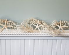 """Beach decor starfish garland using cool IVORY nautical decor netting and large 4-6"""" real white starfish. A nice long 10 foot size too!  Coastal decor Christmas garland, totally wired throughout so you can shape it however you'd like around anything.  This cool nautical netting starfish garland would make a great addition to your Christmas tree, strung on a mantle, on the deck or patio, or on a curtain rod as part of a window treatment.  Free ends.   Measures 10 feet long."""