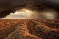 A storm approaches a cut barley field in America.