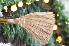Broom close-up with pine branches and light bulbs