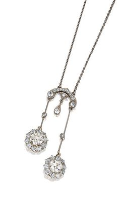 DIAMOND PENDANT NECKLACE, CIRCA 1910. Of négligé design, set with two circular-cut diamonds weighing respectively 1.58 and 1.59 carats, bordered by similar stones, to an arched surmount millegrain-set with circular- and single-cut diamonds, on a fine chain of curb linking, length approximately 470mm.