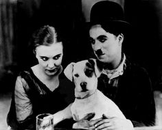 Edna Purviance and director actor Charlie Chaplin with Scraps (real name Mutt) on the set of A Dog's Life (1918).