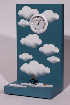 Cloud Bicycle Ride by Pascale Judet. This clock is hand painted with acrylic on MDF, a wood product. The figures are HO scale figures made by Preiser. The clock is signed by the artist on the back. Battery operated.