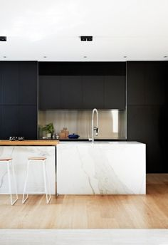 A serene kitchen with black cabinets and a marble island. | japanesetrash.com