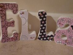 Wood letters with scrapbook paper.  I love this idea!  Hoping to somehow incorporate this idea into the baby's room!!