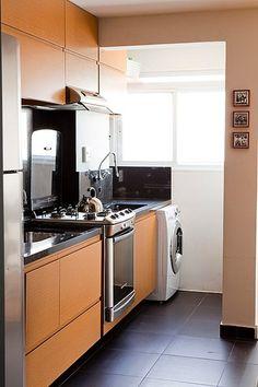 A madeira clara dos armários contrasta com o mármore preto e os eletrodomésticos em inox
