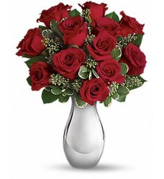 Turn up the heat on a new romance - or a lifelong love affair - with this deluxe red rose bouquet. Ideal for love and romance, it features one dozen of our finest red roses accented with smaller red spray roses and luxuriant greens. It 's all artfully arranged in our stunning Silver Reflections vase.