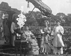 Empress Dowager Cixi 慈禧太后 with attendants on Zhonghai Lake, Beijing, 1903.  n one series of images—taken in the summer of 1903 at Zhonghai, a lake west of the Forbidden City—Cixi adopts the role of Guanyin, the Buddhist bodhisattva of compassion. She sits near an array of potted lotuses, before a painted backdrop of the Purple Bamboo Grove of Guanyin. Her attendants adopt the guises of the bodhisattva's attendants.