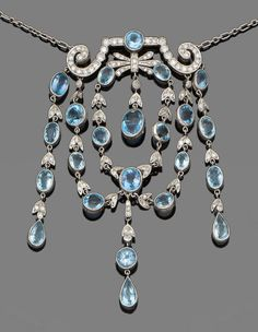 An aquamarine and diamond necklace and a pair of blue topaz and diamond earrings Designed as a scrolling plaque set with single-cut diamonds, suspending swags of circular, oval and pear-shaped aquamarines interspersed with foliate links set with single-cut diamonds, to a trace-link chain, 2nd: Each cut-cornered step-cut blue topaz, to a brilliant-cut diamond surmount.