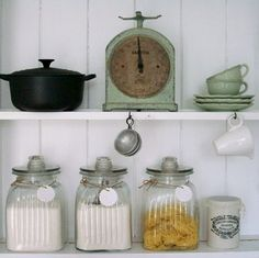 vintage storage cannisters and old weighing scales on kitchen shelf