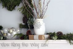 White Vase with Silver snowflake and branches on a Christmas Mantle/mantel