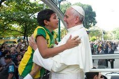El Papa Francisco abraza a un niño emocionado que se acerca a él en la Quinta Boa Vista en Río de Janeiro. (AFP)