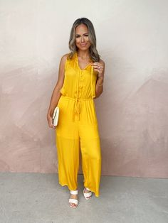 Our Pure Bliss Jumpsuit is perfect for any day and any time! This solid hued one piece features a v-neckline with tie accent, an elastic waist and side pockets. An adjustable waist tie gives the relaxed fit a softly defined look. Finished with front button closures and ruffle trim. Available in three colors. Styled with the Perry Sandal, Follow My Lead Clutch, Impressing Statement Bracelet, and Delicate Soul Necklace. V-neckline with ruffle trim and tie accent Functional front buttons Side… Ankle Length Pants, Ruffle Trim, Fashion Boutique, Hue, Casual Wear, Hot Pink, Jumpsuit, One Piece, Pure Products