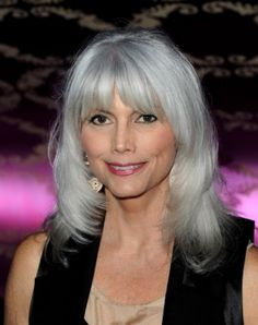 Emmylou Harris' trademark gray hair is a flashy shade of bright silver, which she keeps youthful with an up-to-date 'do that frames her pretty face with bangs and layers