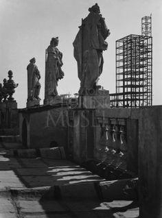 Torino, luglio 1933. Veduta della struttura metallica della Torre Littoria completata dal tetto di Palazzo Madama, con le statue di coronamento in primo piano.