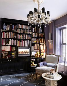 """Kaihoi built the floor-to-ceiling bookcase himself and painted it high-gloss Black by Fine Paints of Europe. The floor, painted to mimic a rug, is Hale Navy and White Down, both by Benjamin Moore. """"Big furniture makes a small room seem grander,"""" says Kaihoi."""