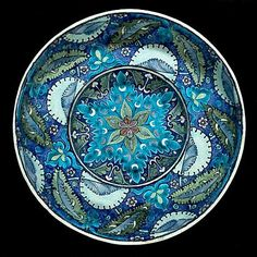 "William de Morgan, Charles Passenger pottery tondino plate.  Fulham, circa 1890   the red body covered in white glaze, the inside painted with serrated leaves, split palmettes, knots, flowerheads and crecent moons in shades of blue, turquoise, green and manganese, the outside painted with stylised leaves and bands of turquoise and blue, marked ""Fulham WDM"" and maker's mark ""CP"" for Charles Passenger"