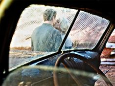 Larsen Apple Farm The couple share a kiss, as seen through the window of a rustic, vintage car.