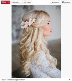 Look romantique et féminin. Sur une chevelure bouclée, réalisez une demi-queue de cheval puis ornez la d'un accessoire fleuri qui sert aussi d'attache