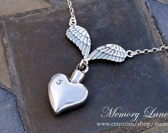 37mm x 8mm silver (stainless steel) cremation urn pendant - Hand stamped sterling silver rectangular charm (If a verse/name is not stated in your checkout notes then Isaiah 41:10 will be stamped on the rectangular pendant) - Sterling Silver angel wing charm - Sterling silver chain This beautiful pendant opens to allow you to place a small amount of cremated remains inside. It can also be used to hold crushed flowers, a lock of hair, dirt or sand from a memorable location, or any other ...
