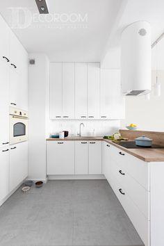 Kuchnia z elementami dwóch stylów: prowansalskiego i nowoczesnego. Drewniany blat i szare, betonowe płytki nawiązują do stylu nowoczesnego, podobnie jak okap dopasowany do kształtu lamp w salonie. Oryginalny piekarnik stylizowany jest na styl prowansalski, tak samo jak klamki i płytki w kształcie cegiełek w pasie roboczym. Kolor baterii i umywalki nawiązuje do koloru piekarnika, a całość spaja dominująca biel.