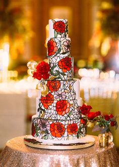 A luxe cake adorned with hand-painted red roses and a stained glass design is a showstopper wedding detail.