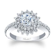 This unique starburst halo engagement ring features a prong set round diamond center encircled with two rows of diamond melee set in a starburst pattern. The dainty shank is adorned with shared prong set diamond running down the shoulders for an elegant finish.