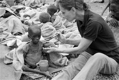 "Audrey Hepburn feeds a high-protein food to a malnourished a child in Baidoa. ""For many it's too late, but for many, many more we can still be on time,"" said Ms. Hepburn, after witnessing the impact of famine on Somalia's children in 1992."