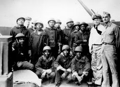 """Negro messmen aboard a United States Navy cruiser who volunteered for additional duty as gunners. They have been doing proficient work under battle conditions on a task force in the Pacific under the instruction of the officers at the right."" July 10, 1942."