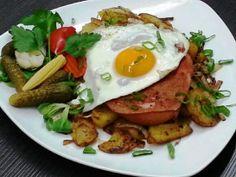 Leberkäse mit Spiegelei. Serviert wird dieses Gericht mit Mixed Pickles und knusprigen Bratkartoffeln für nur 12,10 €.